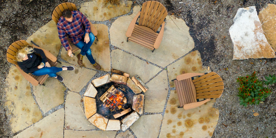 A firepit from above. A man and a woman are relaxing beside the fire.